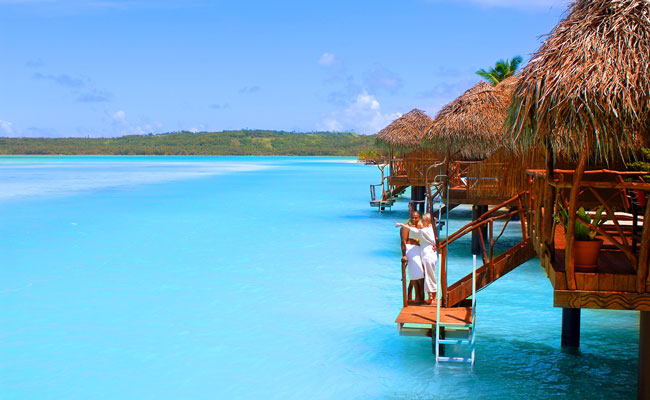 A couple on an overwater bungalow - Aitutaki Lagoon Resort & Spa - Travel South Pacific Beaches
