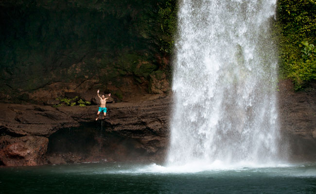 A man jumping into a waterfall - Tourism Fiji - Travel Fiji
